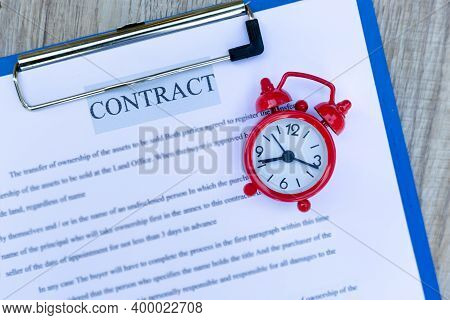 Red Alarm Clock On The Home Purchase Contract, Business Time Concept Making A Contract To Buy A Hous