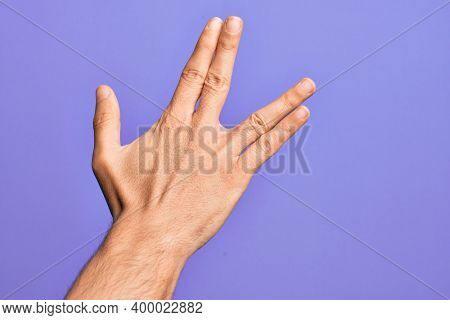 Hand of caucasian young man showing fingers over isolated purple background greeting doing Vulcan salute, showing back of the hand and fingers, freak culture