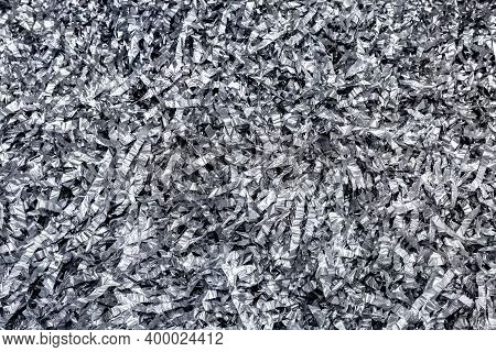 Festive Shiny Silver Tinsel Background. The Texture Of Sliced ​​crumpled Foil.