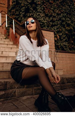 Beautiful Brunette Girl In Sunglasses Sits On The Steps In A Skirt. Fashionable Woman In White Sweat