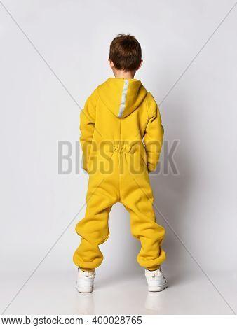 Studio Full Length Portrait Shot Of Little Boy Wearing Yellow Fleece Warm Sportswear Back View Stand