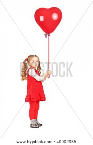 Full length portrait of a little girl holding a red heart shaped balloon isolated on white background