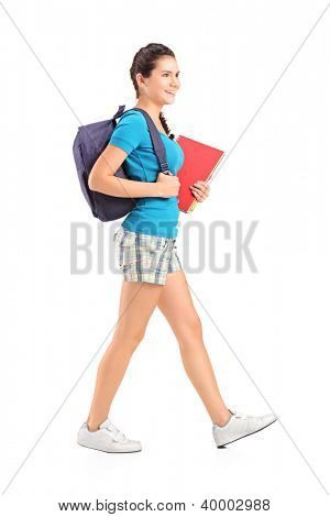 Full length portrait of a female student with backpack walking and holding book isolated on white background