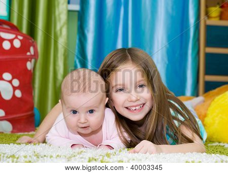 two smiling little sisters at the room