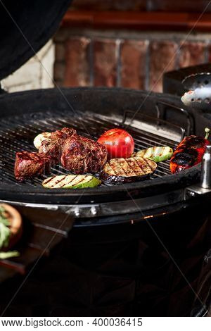 Vegetables And Meat Sizzling On The Grill With Flames