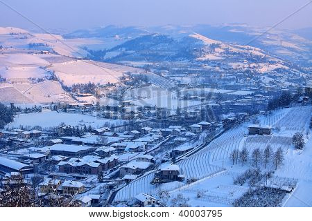 View on small town among snowy hills at sunset in Piedmont, Northern Italy.