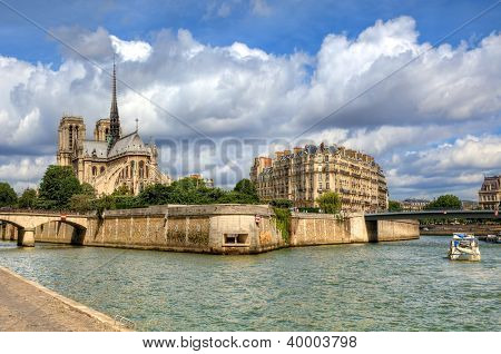 Famous Notre Dame de Paris Cathedral under beautiful cloudy sky in Paris, France (view from Seine river).