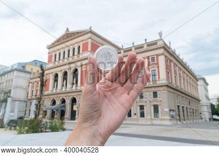 Vienna, Austria - August 30, 2020: Silver Vienna Philharmonic Coin In Man Hand With Blurred Vienna P