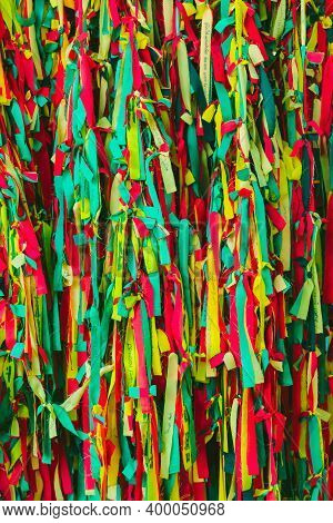 Colorful Scrappy Fabric. Colorful Peaces Of Clothes Be Bind Together On Tree By People Who Believed