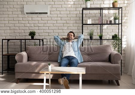 Serene Young Guy Enjoying Breathing Cool Fresh Air Using Conditioner