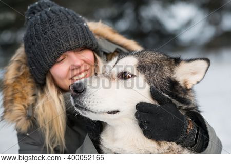Smiling Woman Embracing Alaskan Malamute With Love In Winter Forest . Close Up.