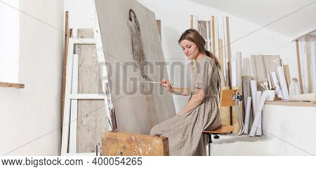 Indoor Shot Of Young Female Artist Sitting In Front Of The Canvas And Painting In Bright White Studi