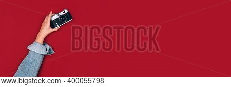 Banner With Female Hand Holding Old Retro Photo Camera On Red Background With Copy Space For Text. T