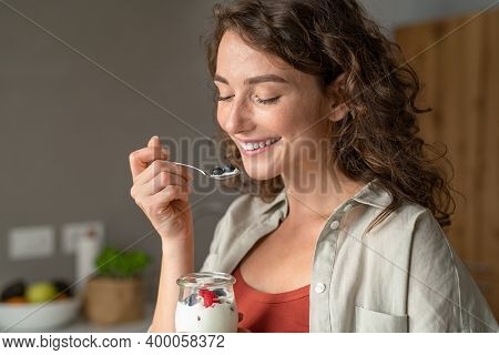 Smiling young woman having healthy breakfast at home with fruit and yogurt. Happy natural girl holding teaspoon with yogurt and blueberries. Beautiful woman eating fresh yoghurt with berries at home.