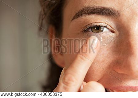 Close up of young woman wearing contact lens with copy space. Young woman holding transparent contact lens on index finger while looking at camera. Close up eye of healthy girl wear contact-lens.