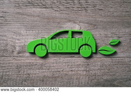 Close up of single green eco-friendly car with leaves silhouette behind. High angle view of wooden cut out of ecofriendly vehicle on wooden table. Concept of green electric car with leaves on plank.
