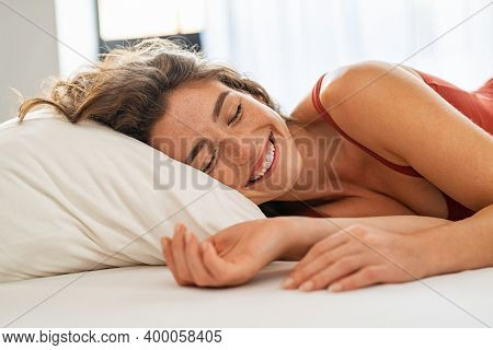 Young beautiful woman sleeping in bed and relaxing in the morning. Close up face of attractive woman in pajamas waking up in comfortable bed. Portrait of lovely girl enjoying time after sleeping.