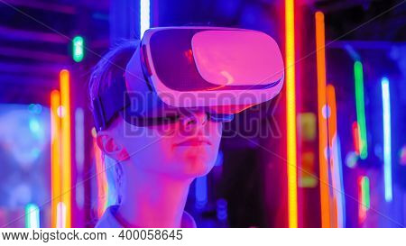 Woman Using Virtual Reality Headset And Looking Around At Interactive Technology Exhibition With Col