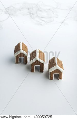 Three Small Gingerbread Houses On White Background. Christmas Baked Goods
