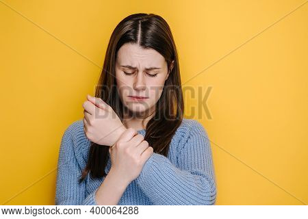 Tired Unhealthy Young Female Massaging Painful Hand, Suffering Carpal Tunnel Syndrome, Dressed In Bl