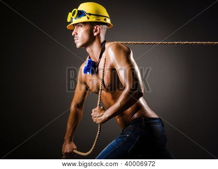 Nude builder pulling rope in darkness