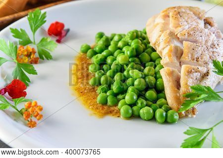 Fried Chicken Breast And Broiled Green Peas On The Festive Decorated White Dish Closeup. Healthy Med