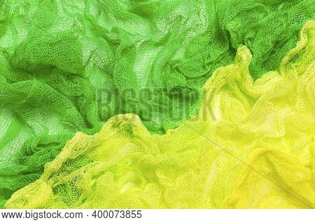 Bright Two-tone Background Of Crumpled Colored Gauze. Yellow And Green Gauze. Used In Design For Dec