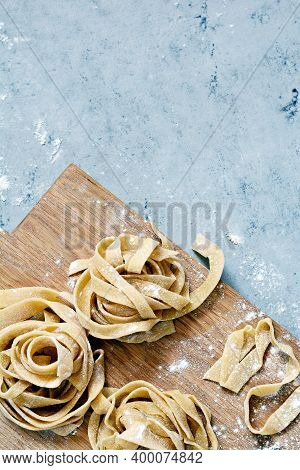 Raw Yellow Homemade Italian Pasta Pappardelle, Fettuccine Or Tagliatelle On A Blue Background, Close
