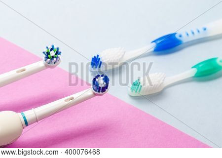 Brushing Heads Of Two Professional Electric Toothbrushes Against Manual Brushes On Pink And Blue Bac