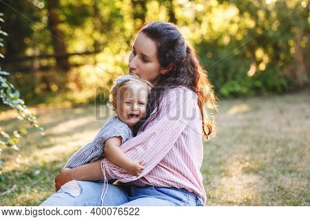 Mother Hugging Pacifying Sad Upset Crying Toddler Girl. Family Young Mom And Crying Baby In Park Out