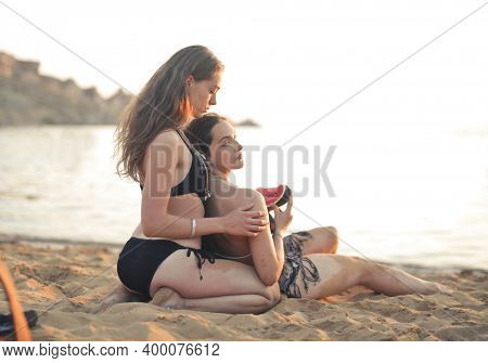 two young women at the beach eat a watermelon