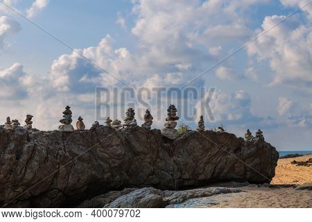 Stacks of stones at rock under cloudy sky, Khao Lak, Thailand.
