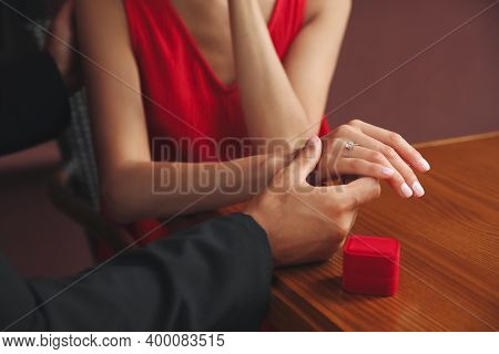Man With Engagement Ring Making Proposal To His Girlfriend At Table, Closeup