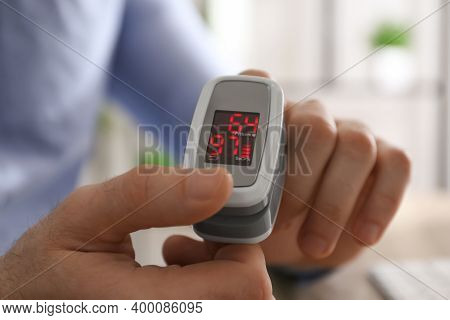 Man Measuring Oxygen Level With Modern Fingertip Pulse Oximeter At Workplace, Closeup