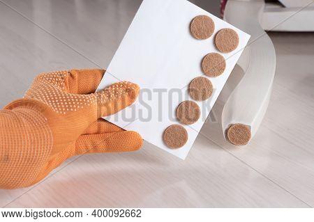 Anti-skid Felt Pad Cover Sticking On Wooden Furniture Leg. Hand Holding Set Floor Care Pad. Adhesive