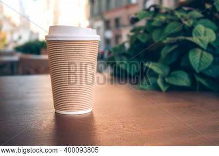 Coffee To Go In Recyclable Paper Cup. Mockup Image Of Paper Cup Of Coffee Take-away, Standing On Woo