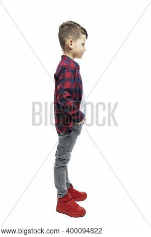 A Boy Of 7 Years Old In Jeans And A Red Plaid Shirt Stands. Full Height. Profile View. Isolated On W