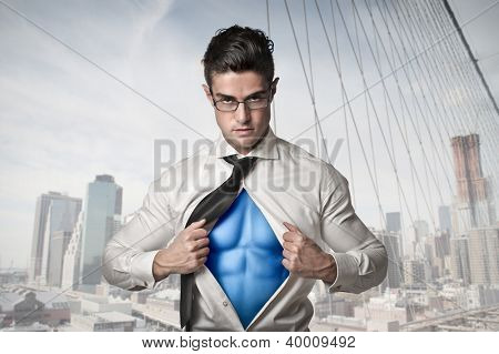 Office worker with glasses opening his shirt like a superhero with the New York skyline in the background