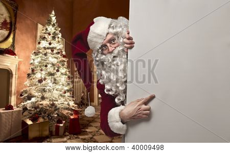 Santa Claus in a house showing something on a white cardboard