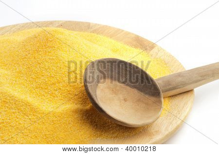 polenta on wooden plate and spoon isolated on white background