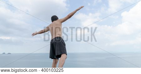 Back View Of Man Opened Hands With Delight At The Ocean And Sky.