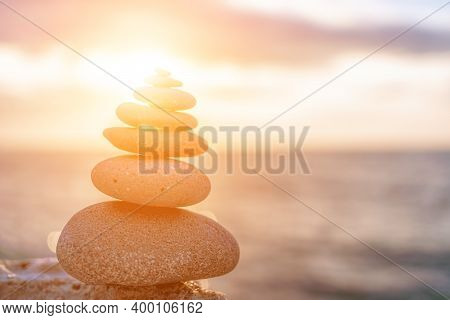 Balanced Rock Pyramid On The Pebble Beach On Sunset. Selective Focus Abstract Bokeh From Sea Foam On