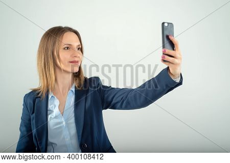 Young Business Lady Makes Selfie On A Cell Phone Isolated On Grey Background