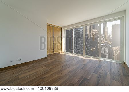 Empty Room With Dark Wooden Floating Laminate Flooring. House Interior, Wide Bedroom Space. New Hous