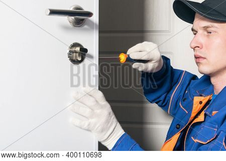 A Man, A Locksmith In Uniform, Repairs The Lock Of The Front Door, Close-up