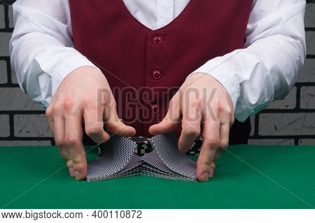 Close-up Of Hands In The Process Of Shuffling Decks Of Cards On The Green Table Before Playing For M