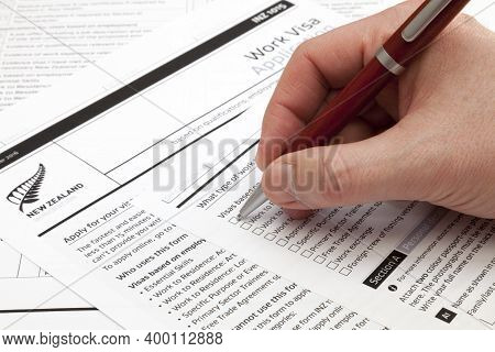 A Man Holding A Ballpoint Pen To Fill A Work Visa Application Form To New Zealand.