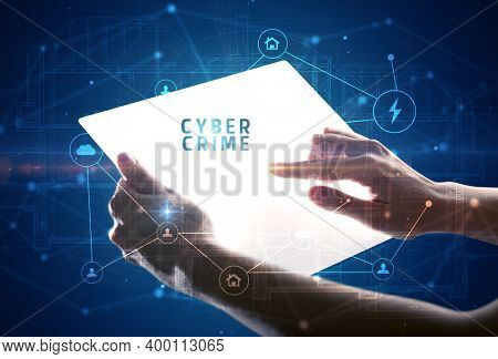 Holding futuristic tablet with CYBER CRIME inscription, cyber security concept