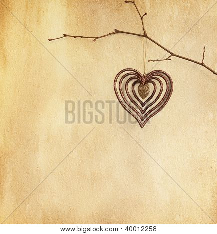 vintage paper  with  heart   hanging  on  branch.