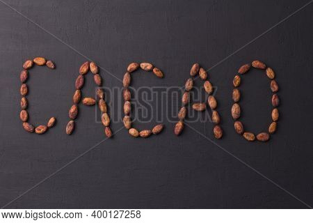 Word Cocoa Is Laid Out On Black Background Made From Natural Unrefined Cocoa Beans. Raw Materials Fo